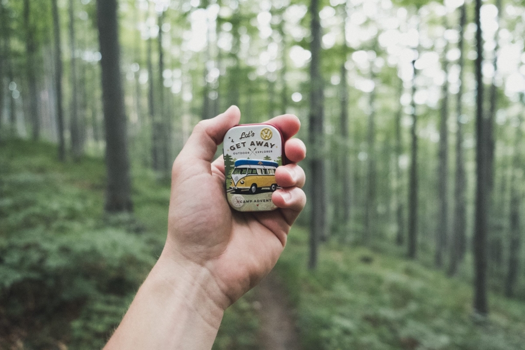 """Hand holding a tin that says """"Let's Get Away"""" in the forest - Holiday Weekends - Jill Griffin Coaching"""