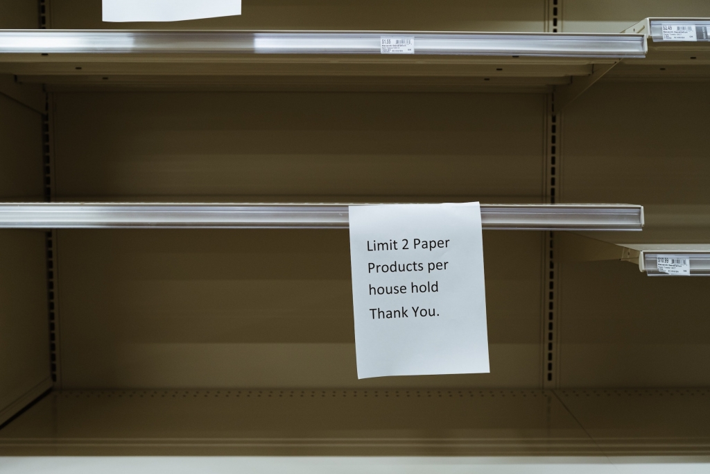 Empty shelves in grocery store with sign - scarcity mindset - Jill Griffin Coaching