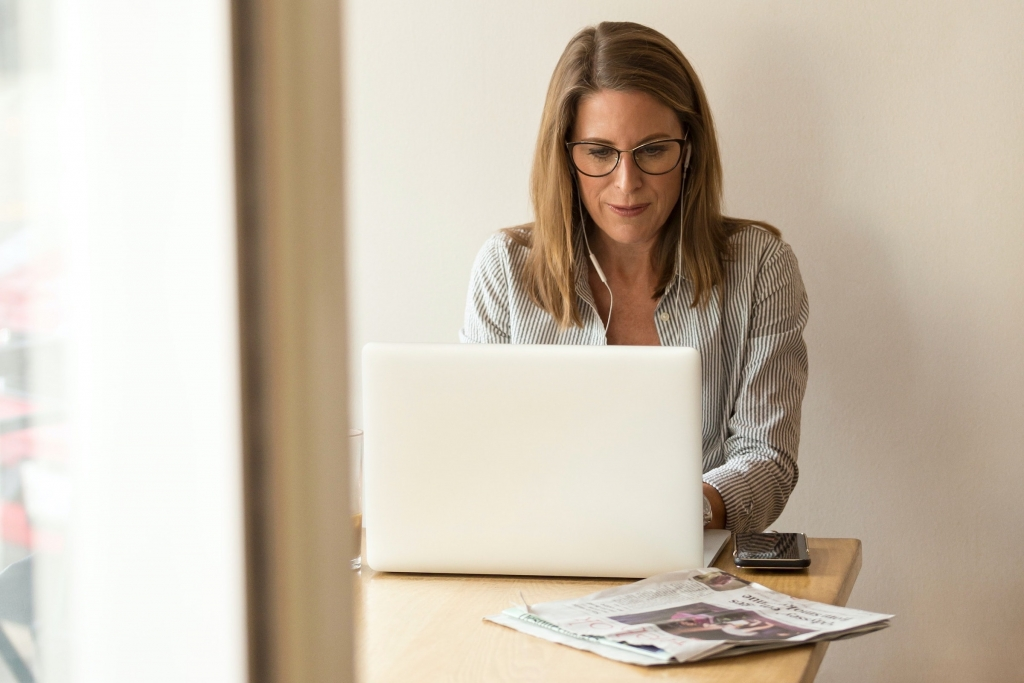 Woman sitting at computer working - how to achieve more Jill Griffin Coaching