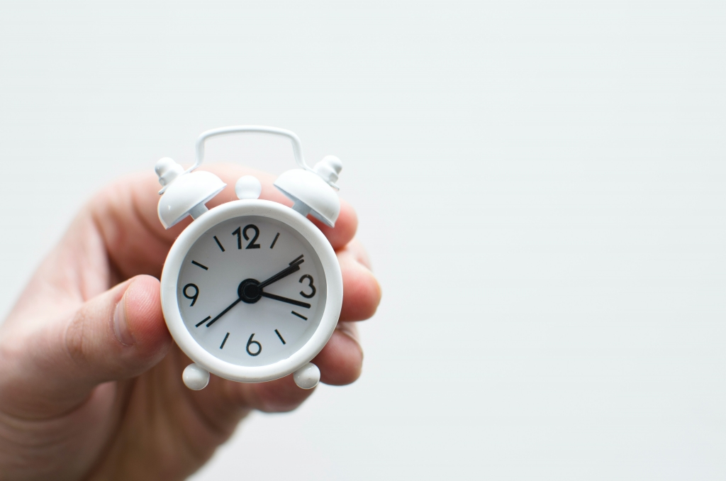 Small white alarm clock in a hand - time management - Jill Griffin Coaching